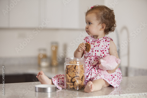 Fotografía Cute baby girl eating cookies from a jar