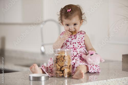 Fotografía Cute little girl eating cookies from a jar
