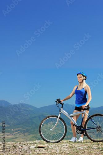 Fototapeta A young female biker posing with a mountain bike obraz na płótnie