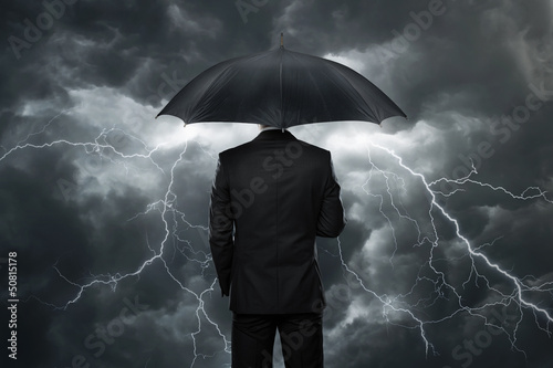 Businessman with umbrella standing in front of storm