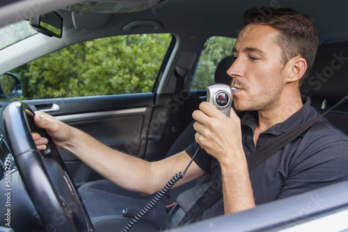 Fotografering  Man blowing into breathalyzer