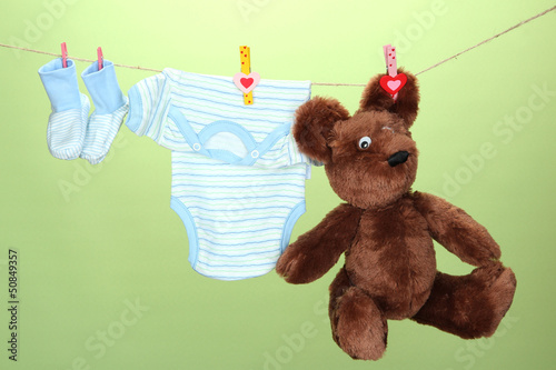 Baby clothes hanging on clothesline, on green background #50849357