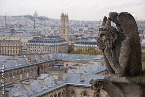 Photo Stone gargoyle overlooking Paris from the Notre Dame