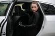 Model sitzt in weißem Auto