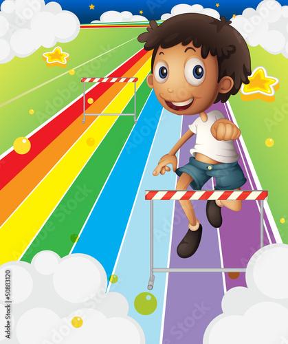 In de dag Regenboog A little boy near the stripe hurdle