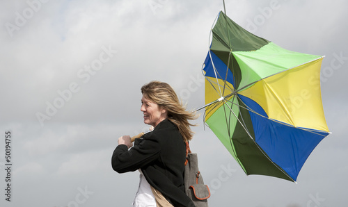 Fotografie, Tablou  Woman struggles with  inside-out umbrella