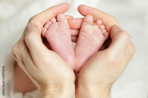 Newborn baby - feet in father hand