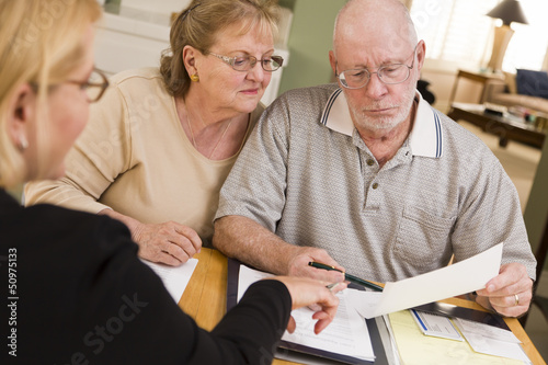 Fotografie, Obraz  Senior Adult Couple Going Over Papers in Their Home with Agent