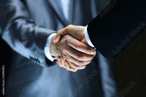 Handshake - Hand holding on black background Canvas Print