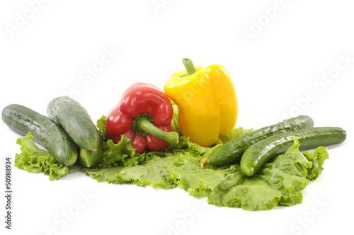 Fotobehang Groenten Fresh vegetables- green cucumber and red and yellow paprika on green lettuce