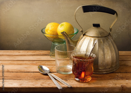 Fotografía  Vintage still life with teapot and lemons on wooden table