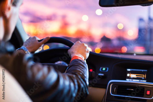 Tableau sur Toile Man driving his modern car at night in a city