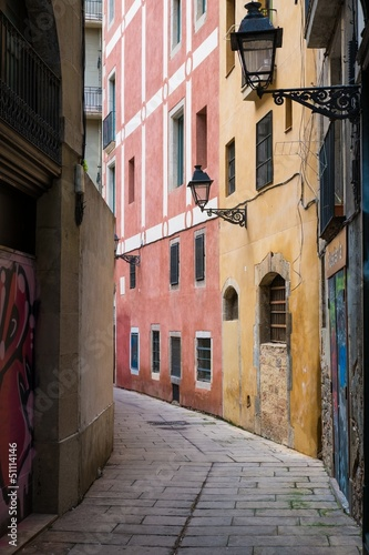 waska-ulica-w-starym-miescie-z-latarniami-ulicznymi