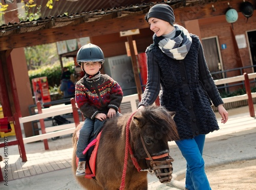 Photo Mother riding her son on a pony