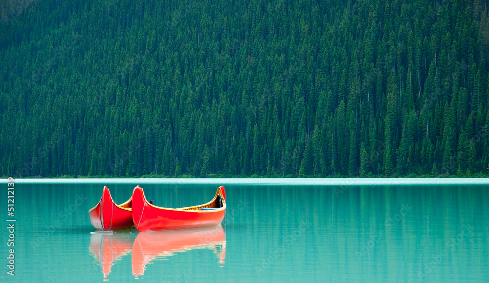 Fototapeta Canoes floating peacufully on Lake Louise near Banff.