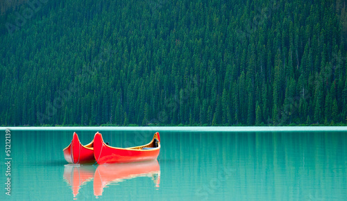Spoed Foto op Canvas Canada Canoes floating peacufully on Lake Louise near Banff.