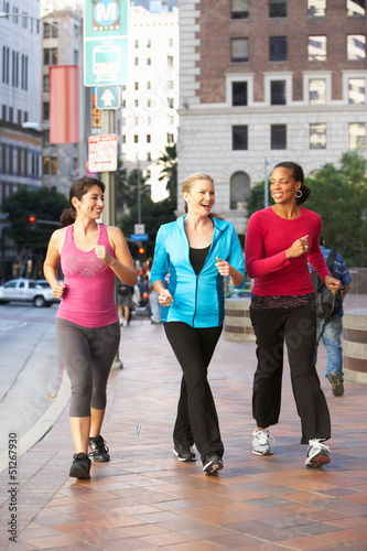 Foto  Group Of Women Power Walking On Urban Street
