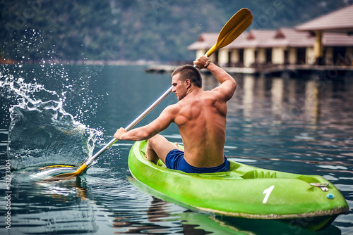 Valokuva  Strong young man in kayak on the picturesque lake in Thailand.