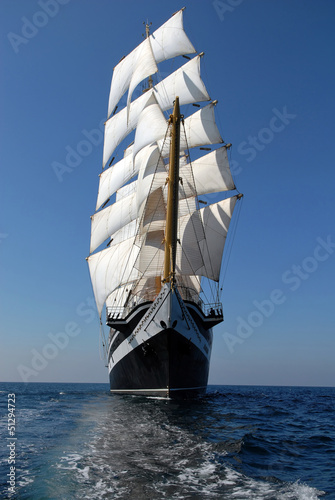 Sailing frigate under full sail in the ocean - 51294723