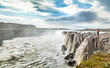 Woman standing near famous Dettifoss waterfall in Iceland