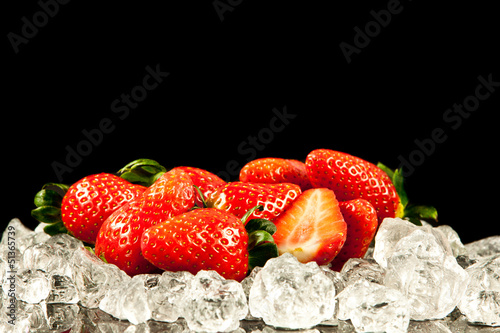 Poster Dans la glace strawberry on black background. strawberries with ice cubes on
