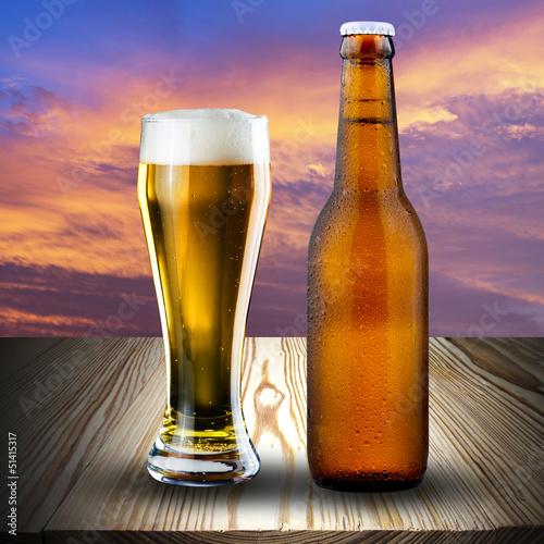 szklo-i-butelka-piwo-na-drewno-stole-przy-zmierzchem