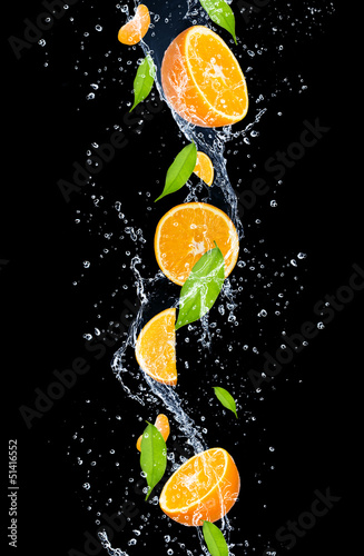 Oranges in water splash, isolated on black background