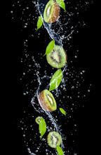 Kiwi Slices In Water Splash, Isolated On Black Background