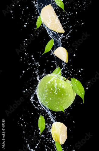 Green apples in water splash, isolated on black background