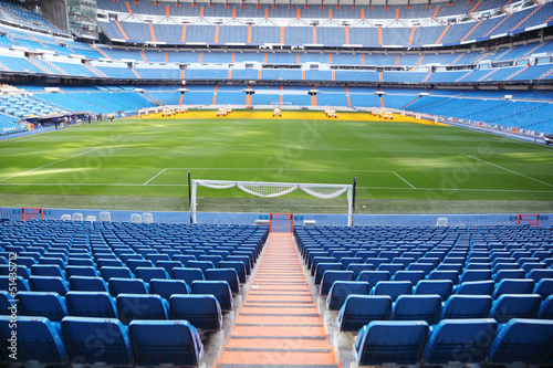Door stickers Stadion Empty football stadium with blue seats, rolled gates