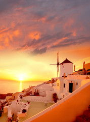 Fototapeta Wschód / zachód słońca Windmill in Santorini against sunset, Greece