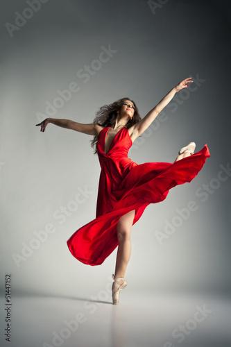 Ballet dancer wearing red dress over grey Fotobehang