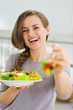 Smiling young woman giving fork with salad