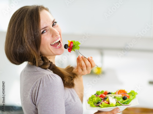 Fototapeta Smiling young woman eating fresh salad in modern kitchen obraz