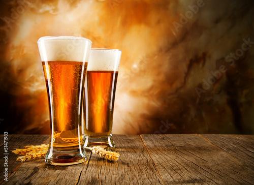 dwie-szklanki-wypelnione-piwem-z-pianka-na-tle-w-brazowych-barwach
