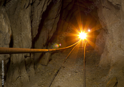 Foto op Aluminium Rudnes Inside abandoned gold mine with shining gold light and ore cart tracks.