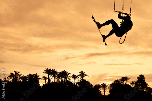 Kiteboarding at sunset. High jump