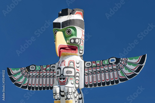In de dag Indiërs A totem wood pole in the blue cloudy background