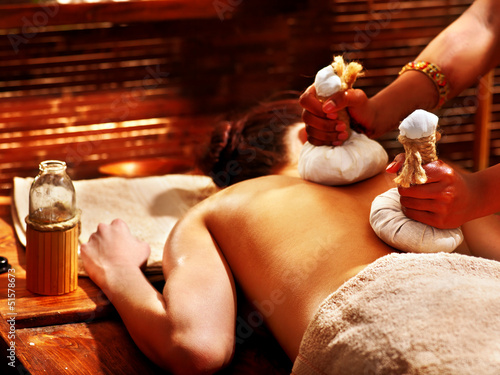 Woman having massage with pouch. - 51578673