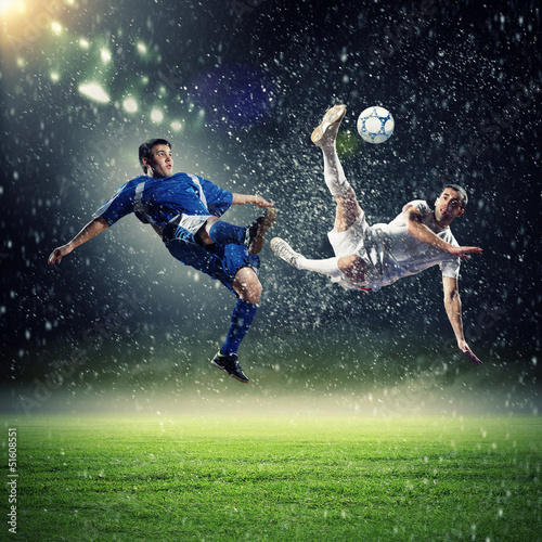 two football players striking the ball - 51608551