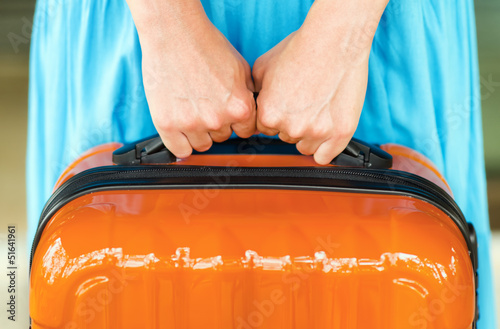 Fotografiet Woman in blue dress holds orange suitcase in hands