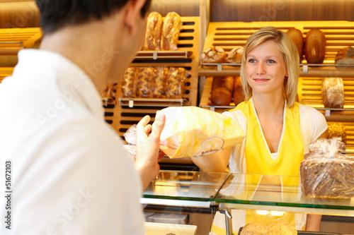 Zdjęcie XXL Sklepikarz piekarni wydaje chleb klientowi