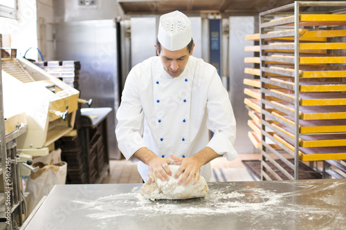 Fotografía Baker kneading dough in bakery