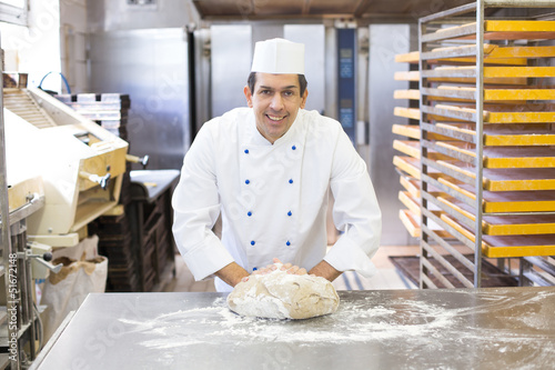 Baker kneading dough in bakery Fototapete