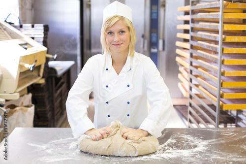 Foto op Plexiglas Bakkerij Baker kneading dough in bakery