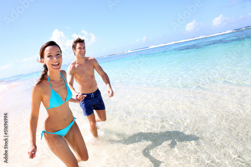 Fotografie, Obraz Couple running on a sandy beach