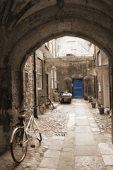 FototapetaBack alley in London, with bikes, blue door at the end