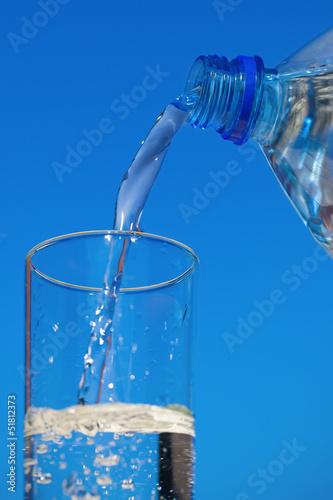 Staande foto Water Water flows from bottle into a glass