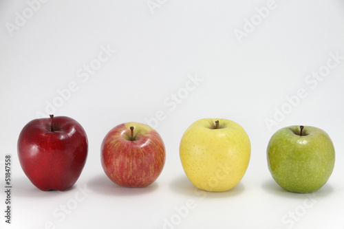 four apples of different color against white background buy this