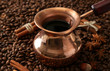 Pot of coffee on coffee beans background